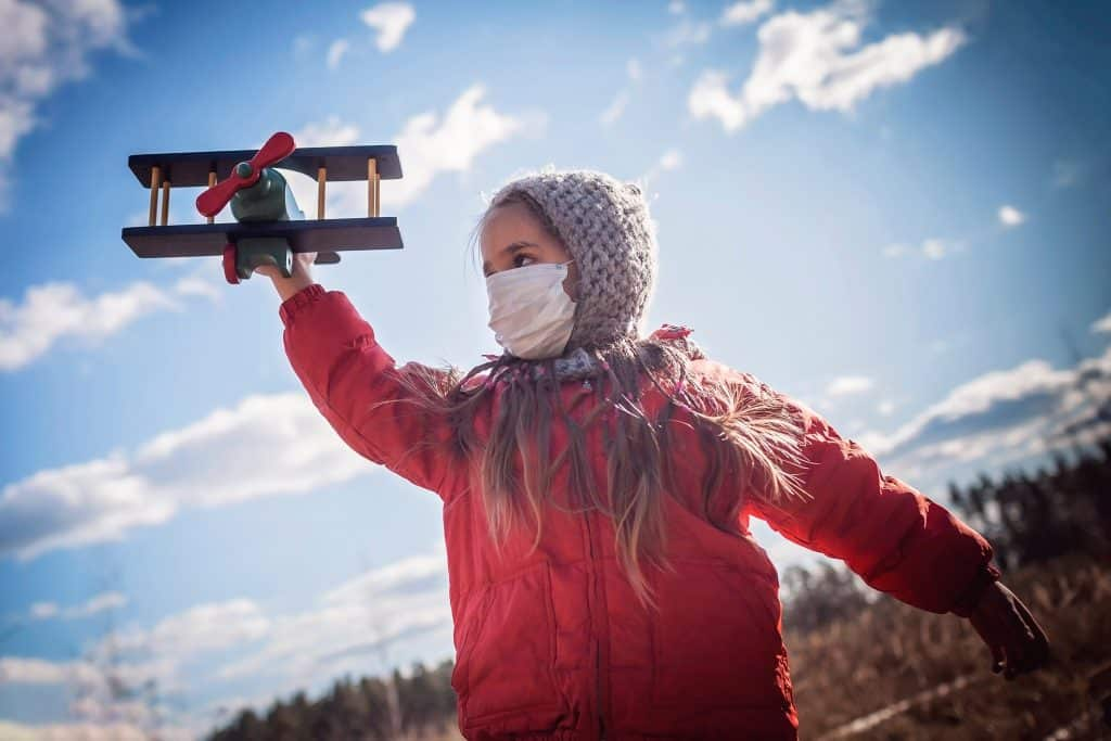 A cute girl wearing respirator mask holding a toy airplane over blue sky background, guideline and life in quarantine time, isolation for stop spreading coronavirus